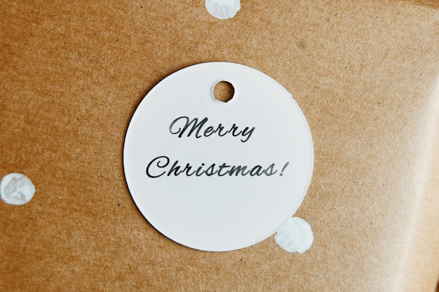 Ronde kartonnen tag met merry christmas inscriptie feestelijk label op ambachtelijk papier met witte polka d...