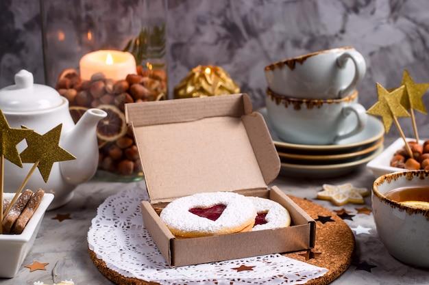 Ronde koekjes met hartvormige jam in een geschenkdoos onder kerstversiering en kaarsen op een grijze tafel