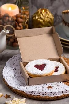 Ronde koekjes met hartvormige jam in een geschenkdoos tussen kerstversiering