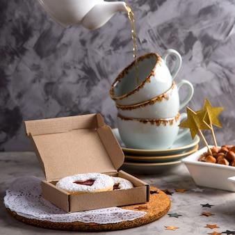 Ronde koekjes met jam in de vorm van een hart in een geschenkdoos onder kerstversiering en sterren op een grijze achtergrond