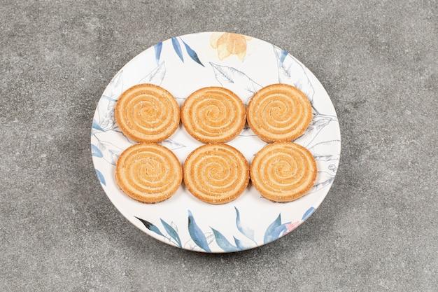 Ronde koekjes met sesamzaadjes op kleurrijke plaat