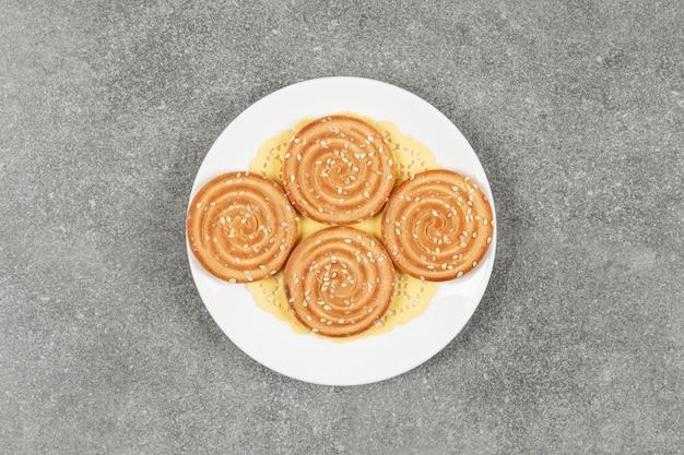 Ronde koekjes met sesamzaadjes op witte plaat