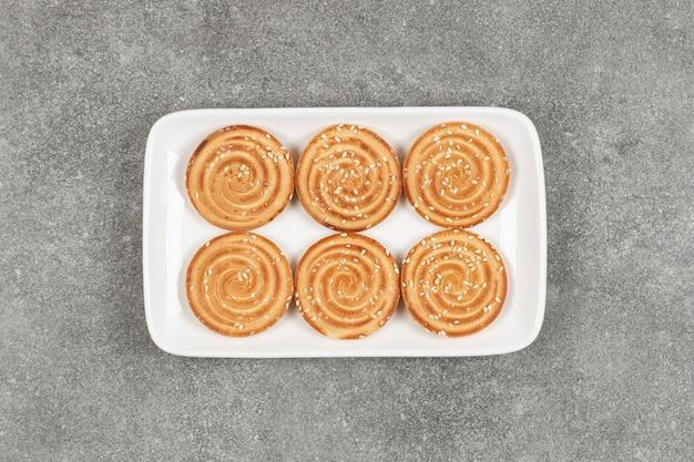 Ronde koekjes met sesamzaadjes op witte vierkante plaat