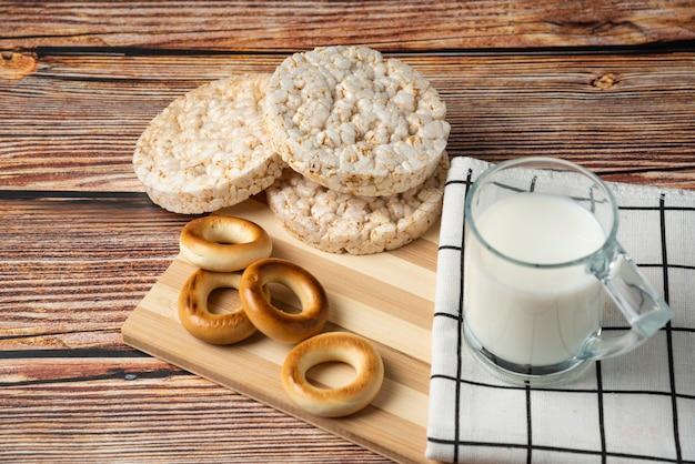 Ronde koekjes, rijstwafels en glas melk op houten tafel.