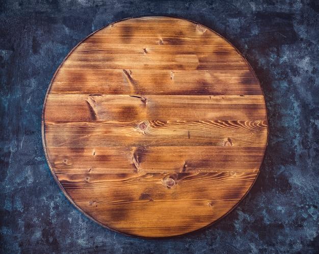 Ronde lege houten snijplank op een donkergrijze gestructureerde achtergrond. bovenaanzicht kopieer ruimte