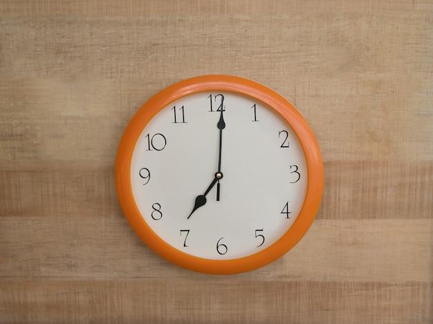 Ronde muurklok op houten muur. zeven uur