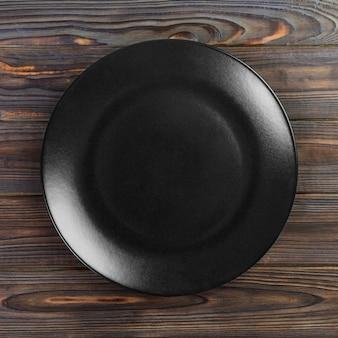 Ronde plaat op tafel, zwarte schotel op hout