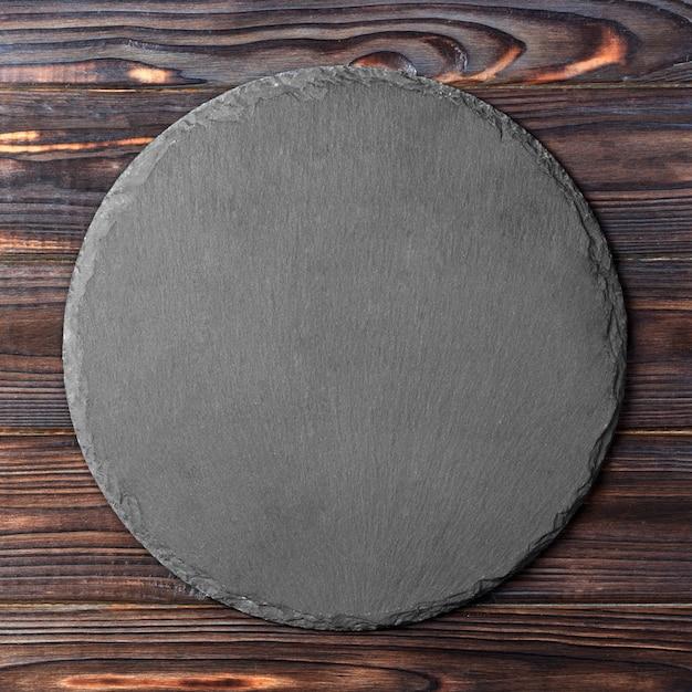 Ronde plaat op tafel. zwarte schotel op houten. kopie ruimte