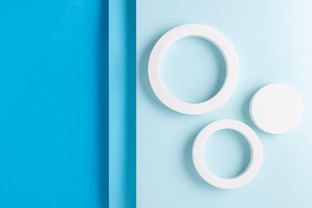 Ronde podia op lichtblauw ontwerp als achtergrond van gevouwen papiermateriaal. bovenaanzicht, plat gelegd.