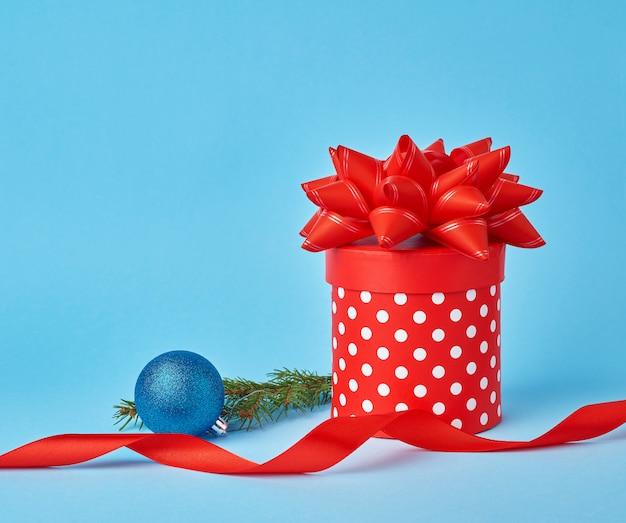 Ronde rode kartonnen doos in witte stippen met een strik, takje sparren met een glanzende blauwe bal