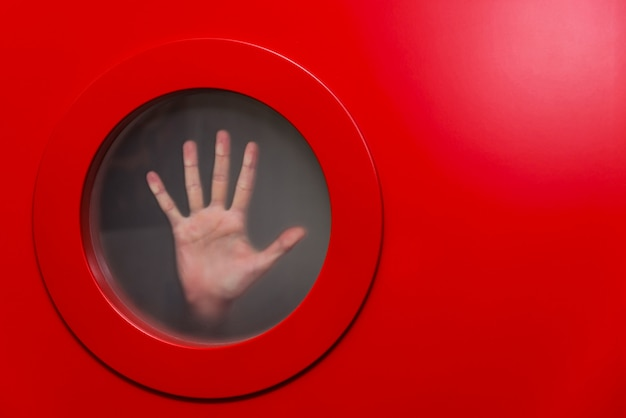 Ronde rode patrijspoort met vrouwelijke hand