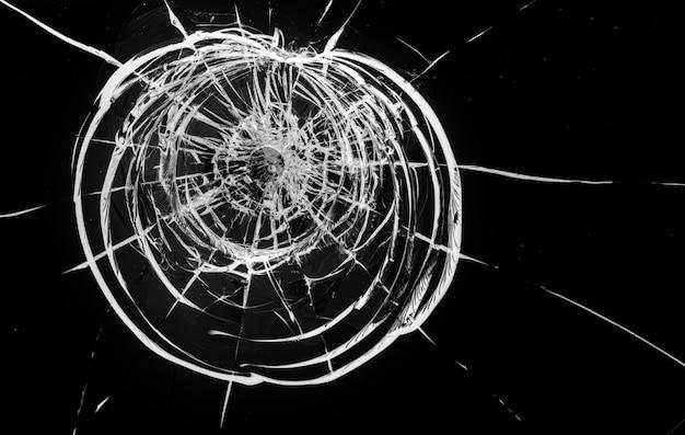Ronde scheuren in glas op zwarte achtergrond. het gat in het glazen oppervlak van de kogel.