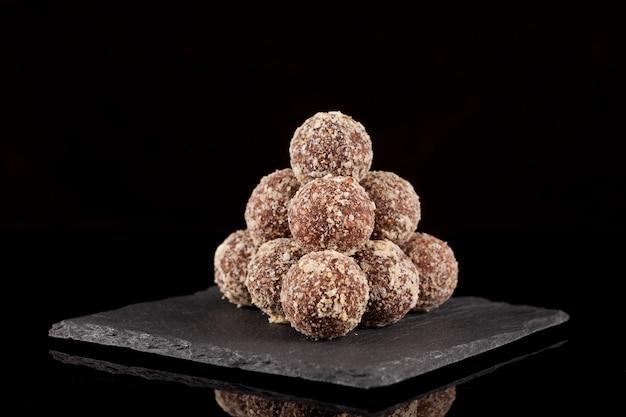Ronde snoepjes gemaakt van noten en gedroogd fruit in piramidevorm op een stenen serveerplank