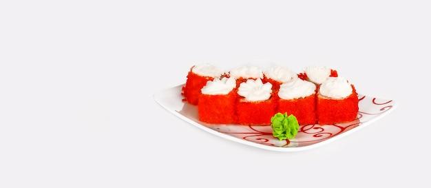 Ronde sushibroodjes met een dop van philadelphia-roomkaas en gegarneerd met rode tobiko-kaviaar op een bord
