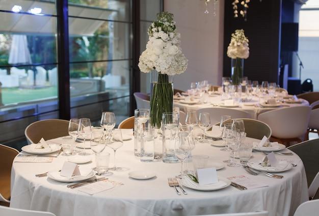 Ronde tafel geserveerd met borden, glas, vork en mes.