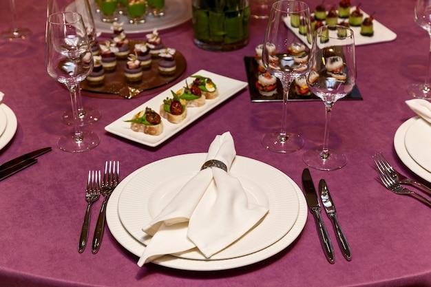 Ronde tafel met roze tafelkleed en bestekset met hapjes voor het banket. horeca, serveertafels voor bonquet