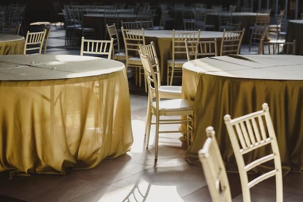 Ronde tafels met tafelkleden, leeg, omgeven door houten stoelen, in een restaurant.