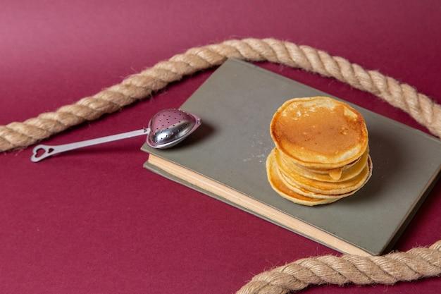 Ronde van de vooraanzicht de lekkere die muffins op het voorbeeldenboek en de roze het ontbijt zoete suiker van de achtergrondvoedselmaaltijd worden gevormd