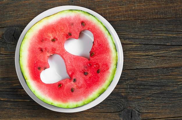 Ronde watermeloenplak met gesneden in de vorm van hart in plaat op oude houten achtergrond, hoogste mening