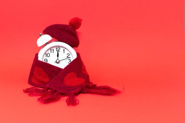 Ronde wekker in gebreide rode muts en sjaal met hartjes. op een rode achtergrond