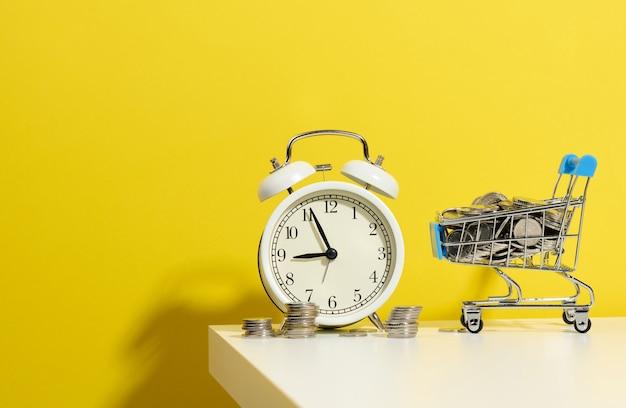 Ronde wekker, miniatuur winkelwagentje met munten op een witte tafel. concepttijd is geld, geldverspilling en armoede