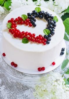 Ronde witte cake met bessen in de vorm van harten, valentijnsdag, op witte ondergrond. afbeelding voor een menu of een zoetwarencatalogus. bovenaanzicht