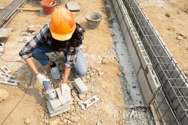 Ronde zaag in de handen van de bouwer, werk aan het leggen van bestrating platen.