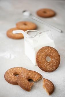 Ronde zandkoekkoekjes met suiker en koude melk op een witte lijst