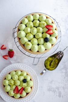 Ronde zandkorstcake met groene pistachecrème en aardbeienjam