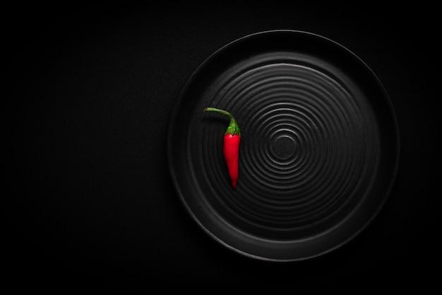 Ronde zwarte keramische plaat met patroon van cirkels met rode verse chili peper
