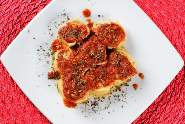 Rondelli gegarneerd met rode saus en besprenkeld met kruiden.