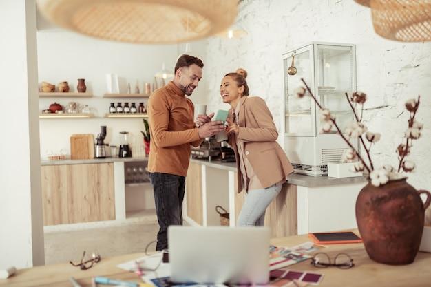Rondkijken. twee vrolijke collega's die koffie drinken in de keuken en samen lachen terwijl ze naar de smartphone kijken.
