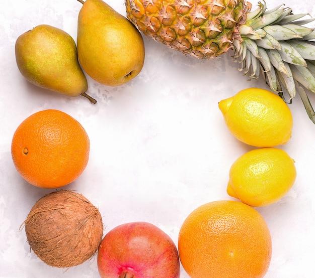 Rondom liggen tropische vruchten op een betonnen grijze ruimte. kopieer ruimte. zomer concept