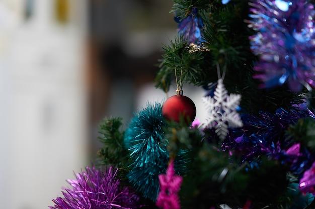 Rood bauble decor op kerstboom met kleurrijke sneeuwvlok