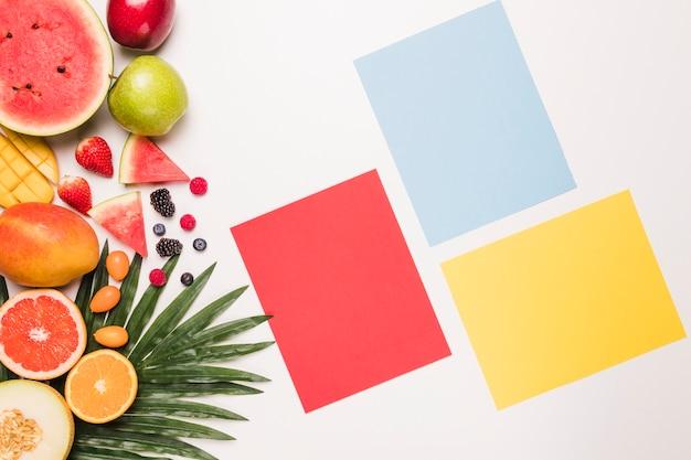 Rood blauw gele kleverige nota en verschillende vruchten bij palmblad