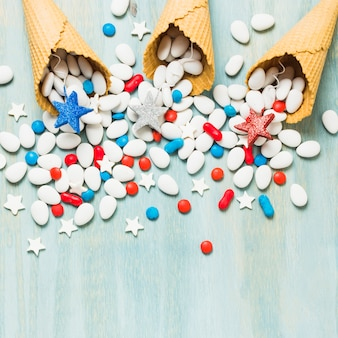 Rood; blauwe en zilveren ster rekwisieten en kleurrijke snoepjes gemorst uit wafel kegel op blauwe gestructureerde achtergrond