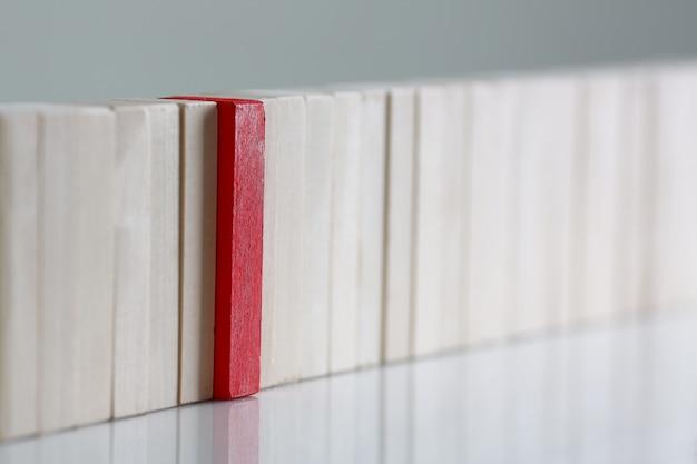 Rood blok in een lijn met houten blokken