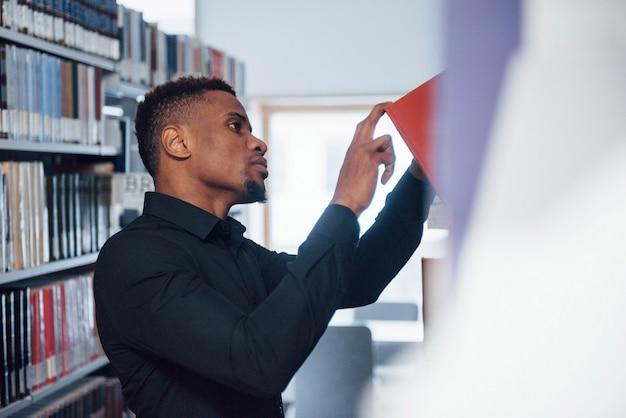 Rood boek plukken. afro-amerikaanse man in de bibliotheek op zoek naar informatie