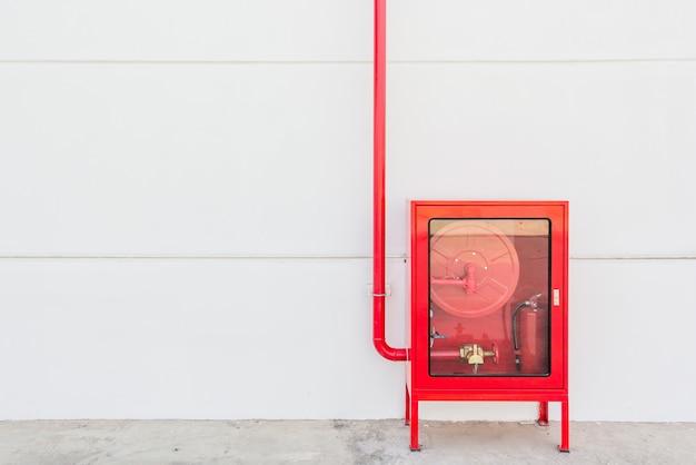 Rood brandslangkabinet en brandblusapparaat op witte muur in de nieuwe de bouwfabriek