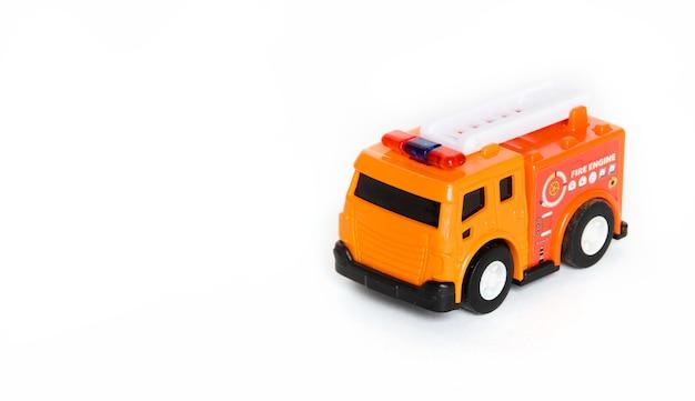 Rood brandweerwagenstuk speelgoed dat over een witte achtergrond wordt geïsoleerd. brandweerwagen speelgoed.