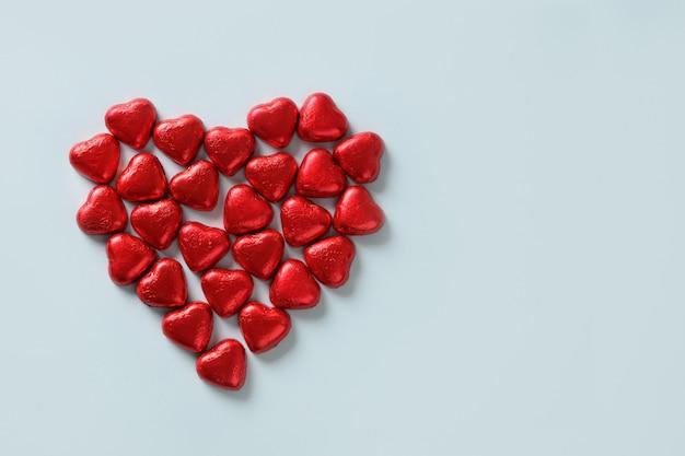 Rood chocoladehart van snoepjes op blauw. valentijnsdag wenskaart.