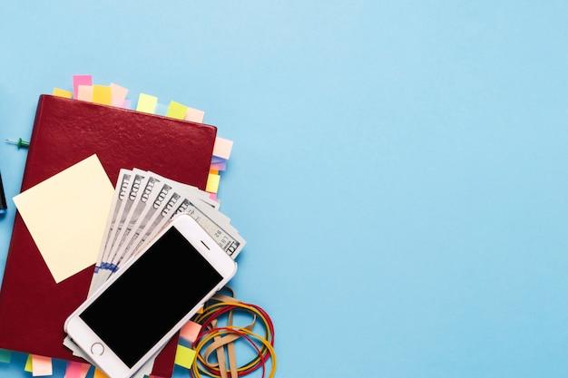 Rood dagboek met stickers op de pagina's, honderd dollar biljetten, briefpapier, witte telefoon, blauwe achtergrond. concept van een succesvol bedrijf, goede planning, time management. plat lag, bovenaanzicht