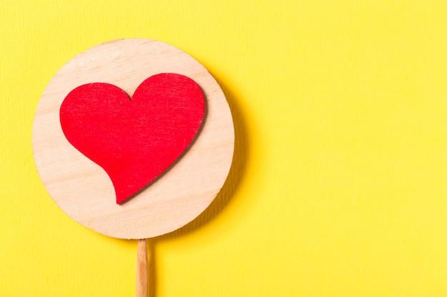 Rood decoratief hart met een stok op geel