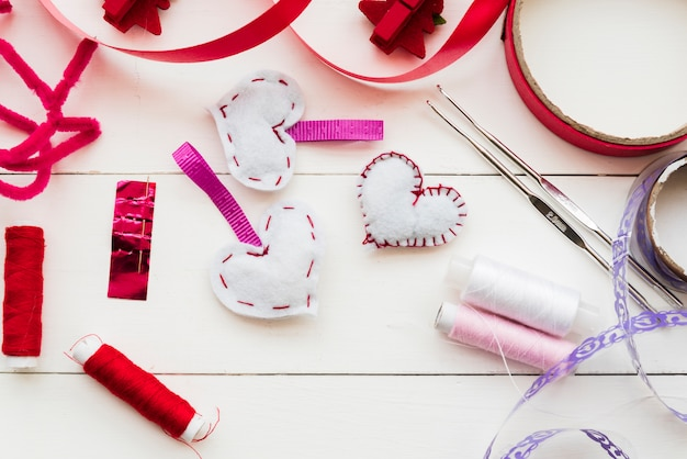 Rood en paars lint; spoelen; haaknaald en hartvorm op witte plank