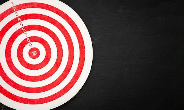 Rood en wit dartbord dat met rimpels op een zwarte houten achtergrond wordt gevuld.