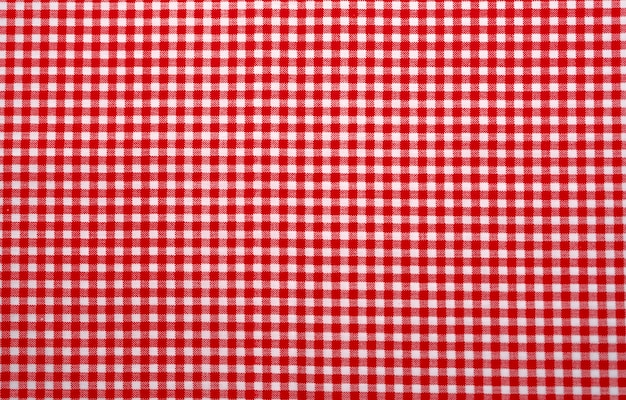 Rood en wit geruit tafelkleed. bovenaanzicht tafelkleed textuur achtergrond. rode gingangpatroonstof. picknickkleed textuur.