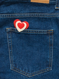 Rood en wit hart in de zak van heldere blauwe spijkerbroek. romantische stijl in modieuze kleding.