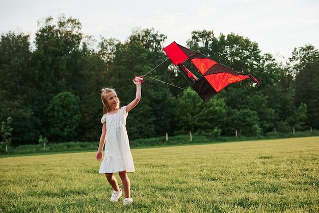 Rood en zwart gekleurde vlieger. gelukkig meisje in witte kleren veel plezier in het veld. prachtige natuur.