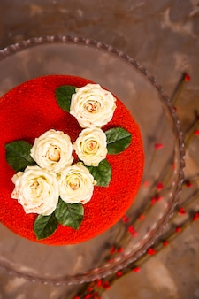 Rood fluwelen cake versierd met witte kleine rozen met groene bladeren