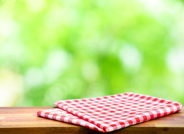 Rood gecontroleerd tafelkleed op hout met groene bokeh van boomachtergrond vervagen